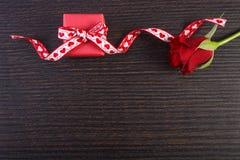 Το τυλιγμένο δώρο με την κόκκινη κορδέλλα και αυξήθηκε για την ημέρα βαλεντίνων, διάστημα αντιγράφων για το κείμενο Στοκ φωτογραφία με δικαίωμα ελεύθερης χρήσης