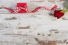 Το τυλιγμένο δώρο με την κόκκινη κορδέλλα και αυξήθηκε για την ημέρα βαλεντίνων, διάστημα αντιγράφων για το κείμενο Στοκ Εικόνες