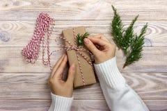 Το τύλιγμα γυναικών παρουσιάζει για τα Χριστούγεννα Χέρια της γυναίκας που διακοσμεί το κιβώτιο δώρων Χριστουγέννων Στοκ εικόνες με δικαίωμα ελεύθερης χρήσης