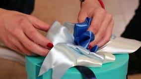 Το τύλιγμα δώρων, κορίτσι πλέκει το τόξο σε ένα κιβώτιο με ένα δώρο, μια έκπληξη διακοπών για τα Χριστούγεννα ή ένα παρόν γενεθλί φιλμ μικρού μήκους
