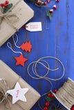 Το τύλιγμα δώρων παρουσιάζει στο σκούρο μπλε πίνακα Στοκ Φωτογραφίες