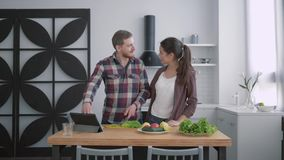 Το υγιές βάρος, ευτυχής σύζυγος με το σύζυγο προετοιμάζει τα θρεπτικά τρόφιμα των λαχανικών και των πρασίνων σύμφωνα με το σχέδιο φιλμ μικρού μήκους