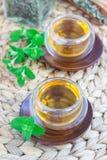 Το υγιές βοτανικό τσάι μεντών στο ασιατικό φλυτζάνι γυαλιού με φρέσκο peppermint και το τσάι εκσκάπτουν στο υπόβαθρο Στοκ φωτογραφία με δικαίωμα ελεύθερης χρήσης