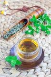 Το υγιές βοτανικό τσάι μεντών στο ασιατικό φλυτζάνι με φρέσκο peppermint και το τσάι εκσκάπτουν στο υπόβαθρο, κάθετο Στοκ Φωτογραφία