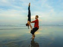 Το υγιές και ελκυστικό κατάλληλο ζεύγος των ακροβατών που κάνουν την ισορροπία και την περισυλλογή acroyoga ασκεί στην όμορφη άσκ στοκ εικόνες