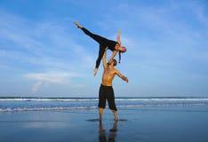 Το υγιές και ελκυστικό κατάλληλο ζεύγος των ακροβατών που κάνουν την ισορροπία και την περισυλλογή acroyoga ασκεί στην όμορφη άσκ στοκ φωτογραφία με δικαίωμα ελεύθερης χρήσης