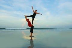 Το υγιές και ελκυστικό κατάλληλο ζεύγος των ακροβατών που κάνουν την ισορροπία και την περισυλλογή acroyoga ασκεί στην όμορφη άσκ στοκ εικόνα