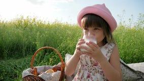 Το υγιές παιδί πίνει το γάλα από το ποτήρι, γλυκό ποτό κοριτσιών από τα γαλακτοκομικά προϊόντα, ευχαρίστηση στο πρόσωπο παιδιών ` απόθεμα βίντεο