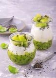 Το υγιές πρόγευμα ή το πρωί τσιμπά με την πουτίγκα και τα μούρα σπόρων chia στο γκρίζο συγκεκριμένο υπόβαθρο πετρών, χορτοφάγος Στοκ Φωτογραφία