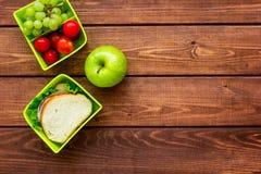 Το υγιές σπάσιμο με το μήλο, το σταφύλι και το σάντουιτς στο καλαθάκι με φαγητό στο επίπεδο εγχώριων πινάκων βάζουν το πρότυπο Στοκ Φωτογραφία