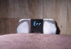 Το υπέρβαρο άτομο εξετάζει ένα σημάδι λάθους μιας κλίμακας στάθμισης Στοκ Φωτογραφία