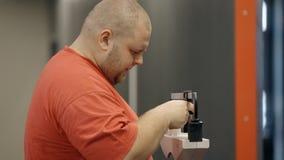 Το υπέρβαρο άτομο στέκεται και χρησιμοποιεί την παλαιά έκδοση της κλίμακας για τη μέτρηση μετά από να εκπαιδεύσει στη γυμναστική απόθεμα βίντεο