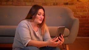 Το υπέρβαρο θηλυκό πρότυπο κάθεται στο πάτωμα που μιλά στο videochat στην ταμπλέτα ενεργά και που γελά στην άνετη εγχώρια ατμόσφα φιλμ μικρού μήκους