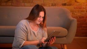 Το υπέρβαρο μακρυμάλλες θηλυκό freelancer κάθεται στο πάτωμα που λειτουργεί με την ταμπλέτα ευχάριστα στην άνετη εγχώρια ατμόσφαι φιλμ μικρού μήκους