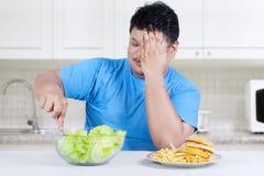 Το υπέρβαρο πρόσωπο επιλέγει να φάει τη σαλάτα 1 Στοκ φωτογραφία με δικαίωμα ελεύθερης χρήσης