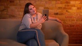 Το υπέρβαρο χαρούμενο θηλυκό πρότυπο κάθεται στον καναπέ που έχει ένα βίντεο καλεί την ταμπλέτα στην άνετη εγχώρια ατμόσφαιρα απόθεμα βίντεο