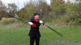 Το υπέρ άτομο στρίβει τα ασιατικά μαύρα μπαστούνια γρήγορα στο δάσος το φθινόπωρο στην slo-Mo φιλμ μικρού μήκους