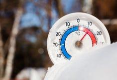 Το υπαίθριο θερμόμετρο στο χιόνι παρουσιάζει στη θερμή θερμοκρασία καυτό ελατήριο εμείς Στοκ εικόνα με δικαίωμα ελεύθερης χρήσης