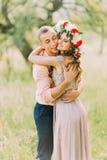 Το υπαίθριο πορτρέτο άνοιξη του νέου ρομαντικού ζεύγους hipster αγκαλιάζει την τοποθέτηση, στον κήπο πόλεων γύρω από τα ανθίζοντα Στοκ Φωτογραφίες