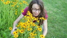 Το υπαίθριο πορτρέτο της νέας όμορφης μοντέρνης γυναίκας μυρίζει τα κίτρινα λουλούδια φιλμ μικρού μήκους