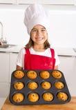 Το υπερήφανο κορίτσι που παρουσιάζει μόνο γίνοντα muffin της συσσωματώνει το ψήσιμο εκμάθησης φορώντας την κόκκινη ποδιά και μαγε Στοκ φωτογραφία με δικαίωμα ελεύθερης χρήσης