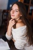 Το λυπημένο κορίτσι κάθεται σε λίγο πίνακα και κοιτάζει προς τα κάτω στοκ εικόνα