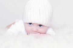 Το λυπημένο μωρό σε ένα άσπρο πλεκτό καπέλο Στοκ φωτογραφία με δικαίωμα ελεύθερης χρήσης