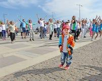 Το λυπημένο ταραγμένο αγόρι κοντά στους χορεύοντας ευτυχείς ανθρώπους Στοκ Εικόνες
