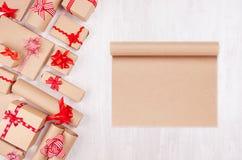 Το υπόβαθρο δώρων εορτασμού με το κενό έγγραφο για το σχέδιο και τη διαφήμιση και διαφορετικός παρουσιάζει με τα αστεία κόκκινα τ στοκ εικόνες
