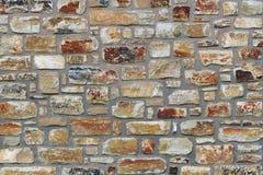 Το υπόβαθρο είναι ένας παλαιός αστικός τοίχος πετρών, μια σύσταση των χειροποίητων πετρών με τις ανώμαλες κιτρινωπές άκρες Στοκ Εικόνες