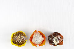 Το υπόβαθρο είναι ξύλινο στο λευκό με τρία διαφορετικά muffins Στοκ Φωτογραφία