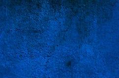 Το υπόβαθρο ενός βαθιού μπλε στόκου έντυσε και χρωμάτισε εξωτερικό, τραχύ που πετάχτηκε του τσιμέντου και το συμπαγή τοίχο Στοκ Εικόνα