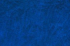 Το υπόβαθρο ενός βαθιού μπλε στόκου έντυσε και χρωμάτισε εξωτερικό, τραχύ που πετάχτηκε του τσιμέντου και το συμπαγή τοίχο Στοκ φωτογραφία με δικαίωμα ελεύθερης χρήσης