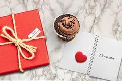 Το υπόβαθρο καρτών ημέρας βαλεντίνων με το κόκκινο παρόν κιβώτιο δώρων στο μαρμάρινο πίνακα δίπλα στη σοκολάτα cupcake αγαπά το μ στοκ εικόνα