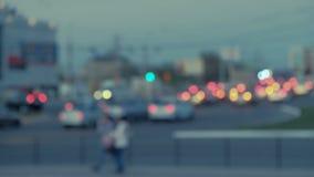 Το υπόβαθρο πόλεων τη νύχτα με τα αυτοκίνητα και τους πεζούς Από την εστίαση το υπόβαθρο με μουτζουρωμένο τα φω'τα πόλεων φιλμ μικρού μήκους