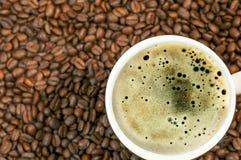 Το υπόβαθρο φασολιών καφέ με το φλυτζάνι του φρέσκου καυτού καφέ κλείνει 1 Στοκ Εικόνες