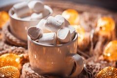 Το υπόβαθρο Χριστουγέννων με το κακάο ή ο καφές με marshmallows σε ένα λευκό κοιλαίνει σε ένα καφετί πλεκτό χειμερινό μαντίλι και Στοκ Εικόνες