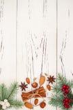 Το υπόβαθρο Χριστουγέννων με παρουσιάζει, κλάδοι έλατου και καρυκεύματα στον παλαιό ξύλινο πίνακα με το διάστημα αντιγράφων Στοκ Φωτογραφία