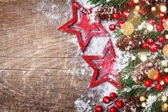 Το υπόβαθρο Χριστουγέννων με τα αστέρια, χιονώδες έλατο διακλαδίζεται, κώνοι και bokeh φω'τα Έμβλημα διακοπών στοκ φωτογραφία