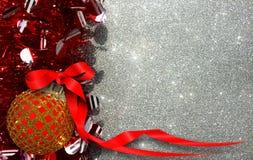 Το υπόβαθρο Χριστουγέννων με την κόκκινη και κίτρινη διακόσμηση σε ένα ασήμι ακτινοβολεί υπόβαθρο στοκ φωτογραφία