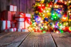 Το υπόβαθρο Χριστουγέννων με τον ξύλινο πίνακα, φως bokeh και παρουσιάζει Στοκ Εικόνα