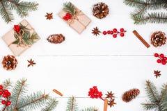 Το υπόβαθρο Χριστουγέννων με το δώρο Χριστουγέννων, έλατο διακλαδίζεται, κώνοι πεύκων, snowflakes, κόκκινες διακοσμήσεις Επίπεδος Στοκ εικόνα με δικαίωμα ελεύθερης χρήσης