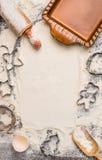 Το υπόβαθρο ψησίματος Χριστουγέννων με το αλεύρι, κυλώντας καρφίτσα, κόπτης μπισκότων και αγροτικός ψήνει την παν, τοπ άποψη, θέσ στοκ φωτογραφία