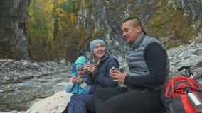 Το υπόλοιπο και πίνει το ζεστό νερό κοντά στον ποταμό βουνών Οικογενειακά ταξίδια Περιβάλλον ανθρώπων από τα βουνά, ποταμοί, ρεύμ απόθεμα βίντεο