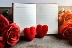 Το υπόμνημα, το σημειωματάριο με το κόκκινο μαξιλάρι καρδιών και η ανθοδέσμη του κοκκίνου αυξήθηκαν Στοκ εικόνες με δικαίωμα ελεύθερης χρήσης