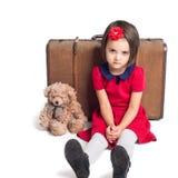 Το δυστυχισμένο όμορφο μικρό κορίτσι με τη βαλίτσα και το παιχνίδι αντέχουν Στοκ Εικόνες