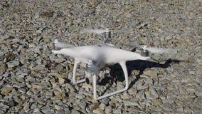 Το φάντασμα 4 κηφήνων του dji επιχείρησης με τους ανοιγμένους προωστήρες στέκεται στο αμμοχάλικο απόθεμα βίντεο