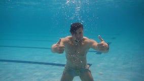 Το φίλαθλο άτομο που κολυμπά κάτω από το νερό σε μια λίμνη και παρουσιάζει αντίχειρες φιλμ μικρού μήκους