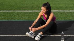 Το φίλαθλο ασιατικό κορίτσι sportswear δένει τα κορδόνια στα πάνινα παπούτσια καθμένος στο στάδιο πρίν εκπαιδεύει απόθεμα βίντεο