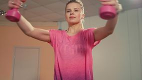 Το φίλαθλο κορίτσι κάνει την άσκηση με τους αλτήρες επάνω σε Workout στη γυμναστική απόθεμα βίντεο